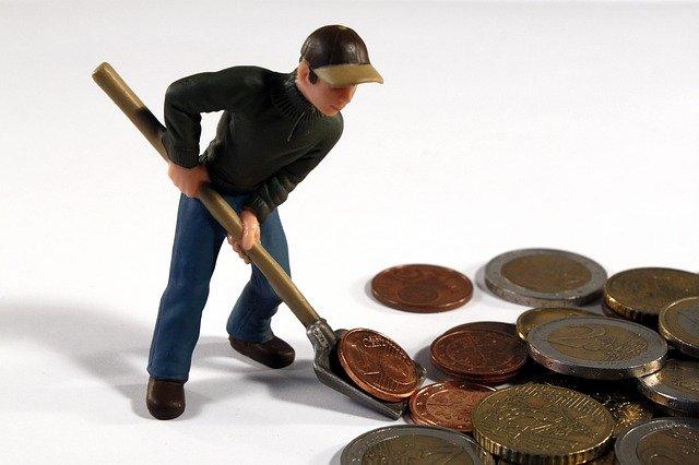 muž s lopatou háže peníze