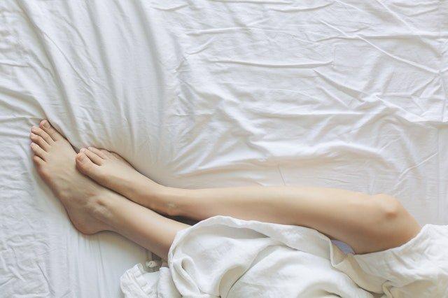 nohy pod bílou přikrývkou na bílém prostěradle