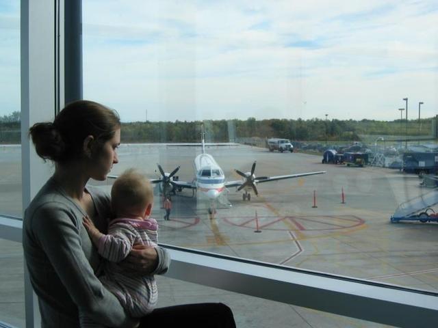 žena s dítětem v náručí u okénka v letištní hale