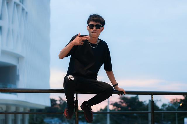chlapec sedící na zábradlí ve městě s černým tričkem