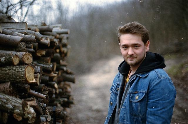 mladík u naskládaného dřeva u lesa