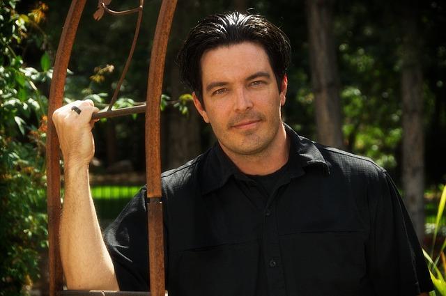 mužský model v černé košili v zahradě